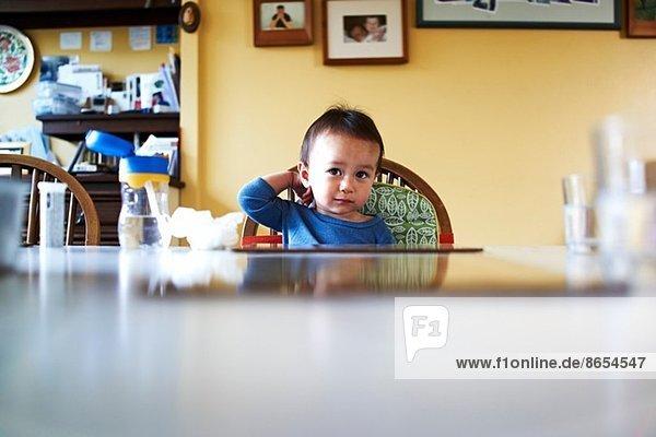 Kleiner Junge sitzt am Küchentisch