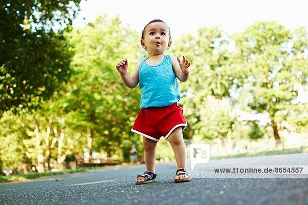 Kleiner Junge steht auf dem Parkweg