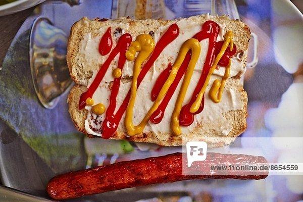 Stilleben von Brötchen  Senf  Tomatensauce und Hotdog-Wurst