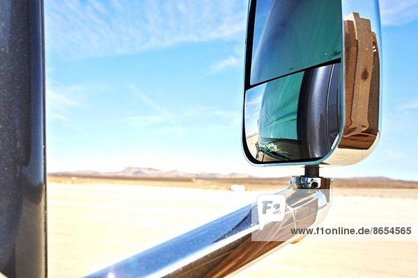 Blick in den Außenspiegel eines Autos  aride Landschaft und ferne Berge