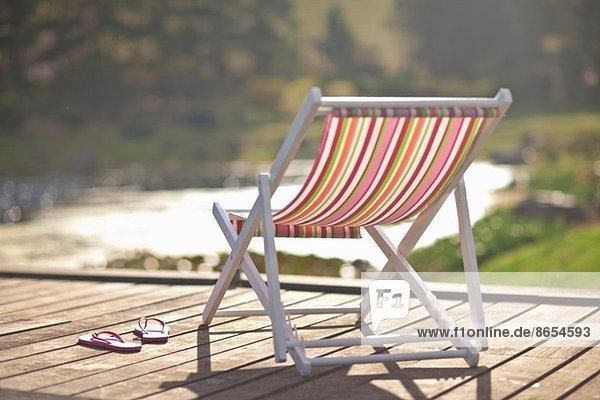 Liegestuhl und Flipflops am Flussufer