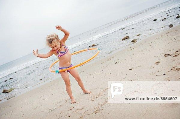 Junges Mädchen mit Hoolahoop am Strand