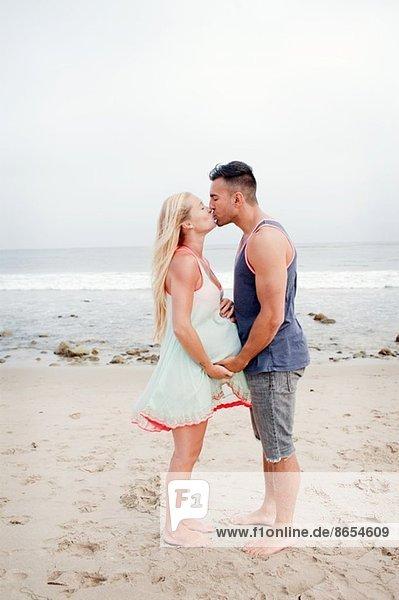 Schwangeres Pärchen beim Küssen am Strand