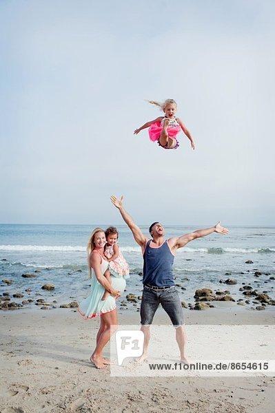 Eltern und zwei junge Mädchen  die am Strand herumalbern.