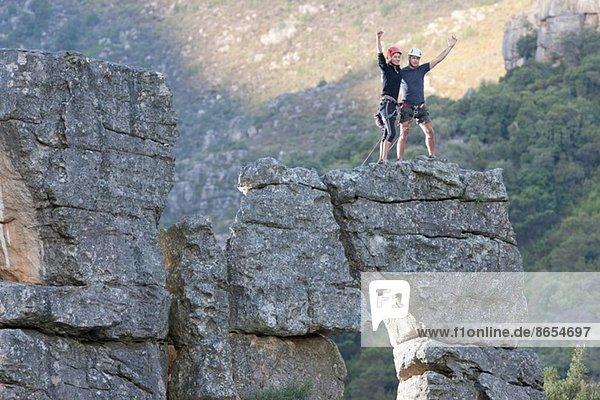 Junges Kletterpaar feiert auf Felsformation