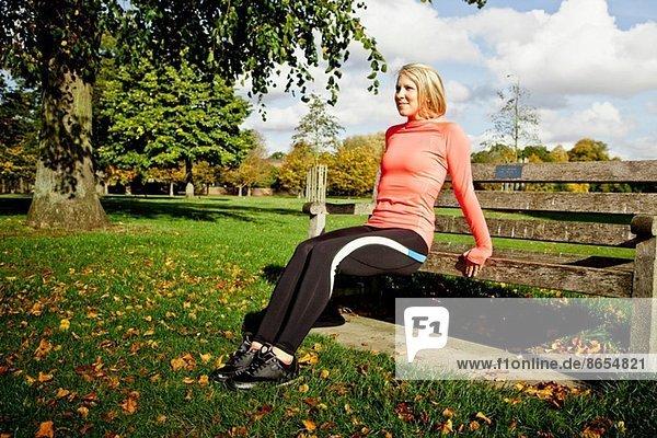 Frau beim Training auf der Parkbank
