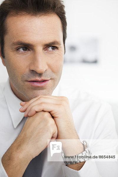 Geschäftsmann mit unter dem Kinn gefesselten Händen  Porträt