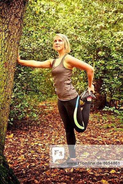 Frau streckt die Beine im Wald aus