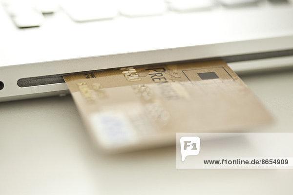 Kreditkarte  die aus der Seite des Laptops herausragt