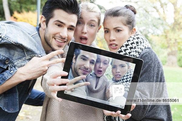 Freunde  die sich mit einem digitalen Tablett im Freien fotografieren.