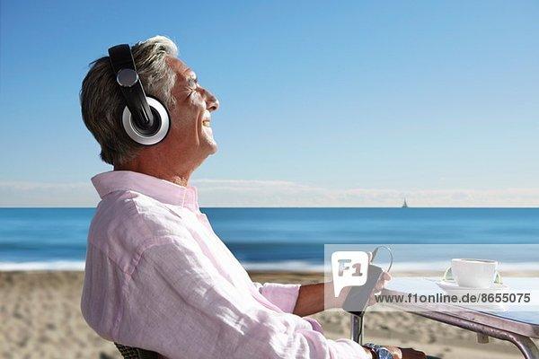 Senior man listening to music with headphones on beach