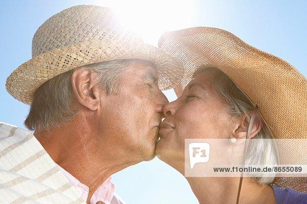 Paar mit Strohhut küssend