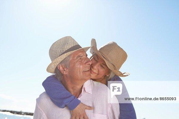 Couple wearing straw hats on beach