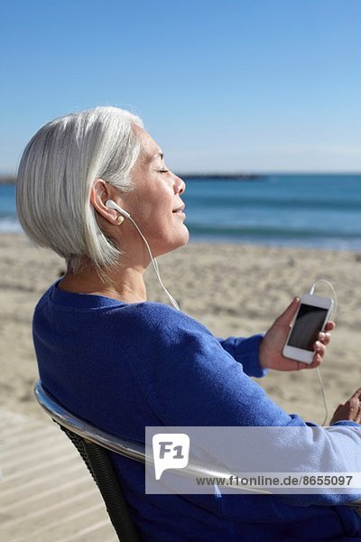 Mature woman listening to music with earbuds on beach