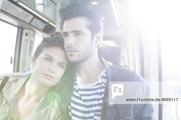 Paar im Zug  Frau stützt ihren Kopf auf die Schulter des Mannes