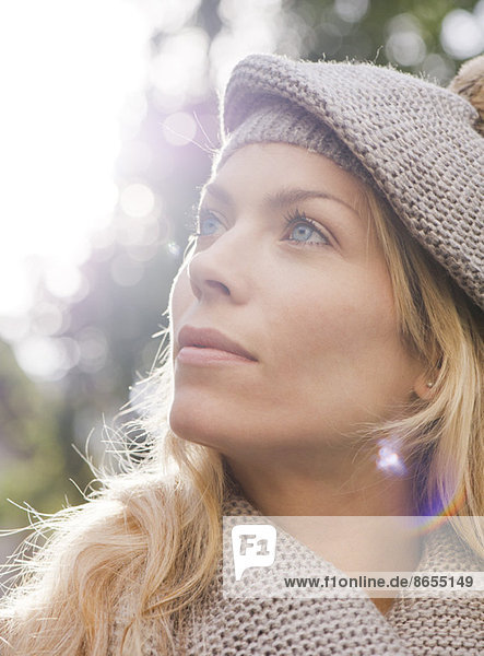 Woman outdoors  looking up in thought  portrait