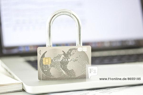 Kreditkarte und Schloss auf dem Laptop  die die Sicherheit des Internets repräsentieren.