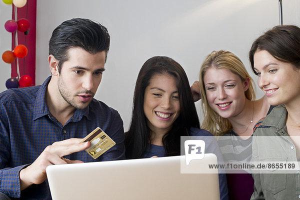 Freunde versammelt um Laptop-Computer Vorbereitung auf die Verwendung von Kreditkarte für den Online-Einkauf