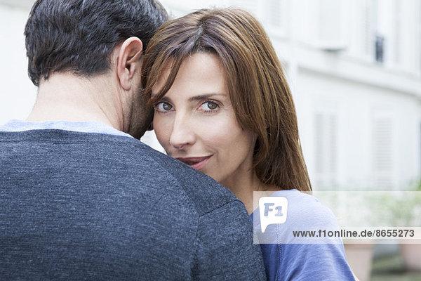 Paar umarmend  Frau mit Blick auf die Kamera