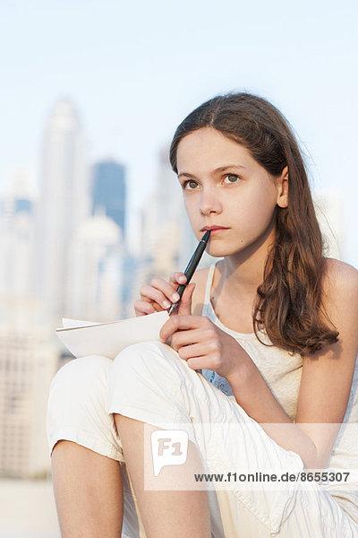 Preteen Mädchen sitzen im Freien mit Stift und Papier  Blick nach oben in Gedanken