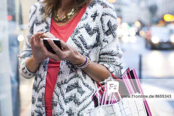 Frau nutzt Smartphone beim Einkaufen