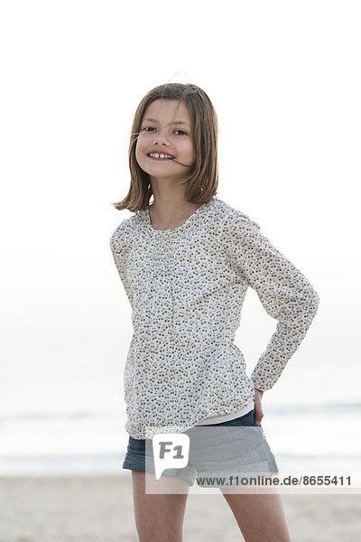 Mädchen am Strand stehend  lächelnd  Portrait