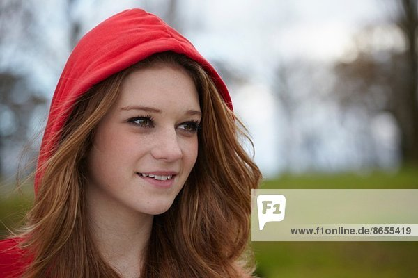 Outdoor portrait of a teenage girl in red hood