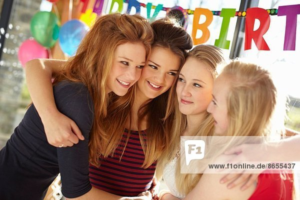 Four teenage girls celebrating at birthday party