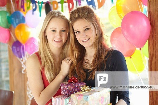 Two teenage girls sharing gifts at birthday party