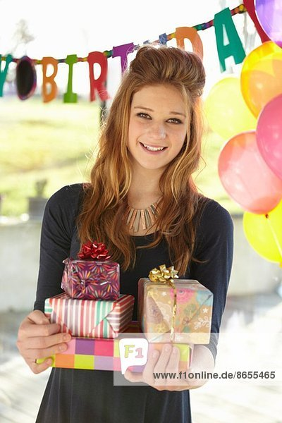 Portrait of teenage girl holding birthday gifts