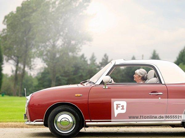 Seniorin im roten Cabriolet unterwegs