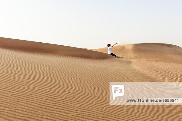 Teenager-Junge sitzt auf einer Wüstendüne und wirft Sand in die Luft.