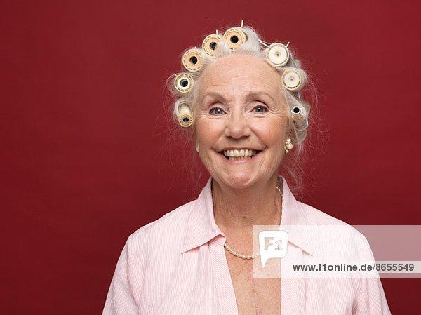 Studio-Porträt einer älteren Frau in Haarrollen
