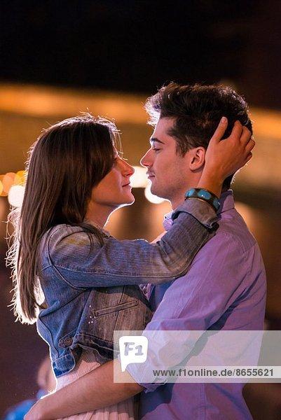 Junges Paar umarmt sich bei Nacht  Paris  Frankreich