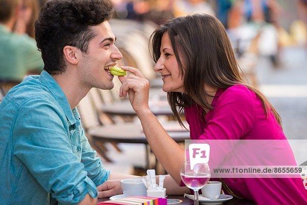 Junges Paar isst Makrone im Straßencafé  Paris  Frankreich