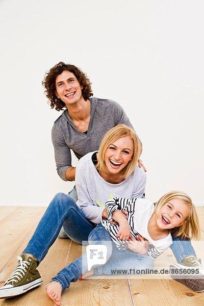 Studioaufnahme eines Paares  das sich mit seiner Tochter amüsiert.