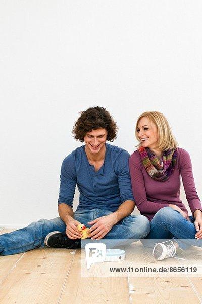 Studioaufnahme eines auf dem Boden sitzenden Paares mit Spielzeug