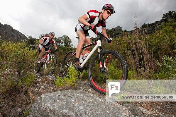 Junges Paar auf Mountainbikes auf Schotterpiste
