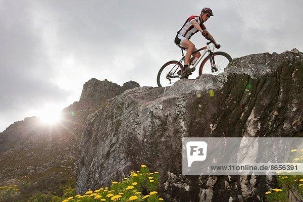 Junger Mann beim Mountainbiken auf dem Gipfel der Felsformation