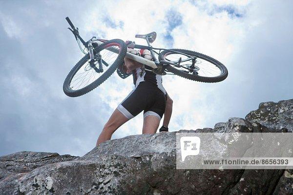 Junger Mann mit Mountainbike auf dem Felsen