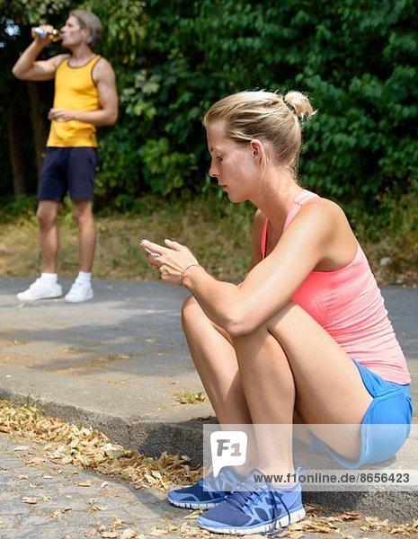 Junge Läuferin sitzt auf dem Bürgersteig und schaut aufs Handy.