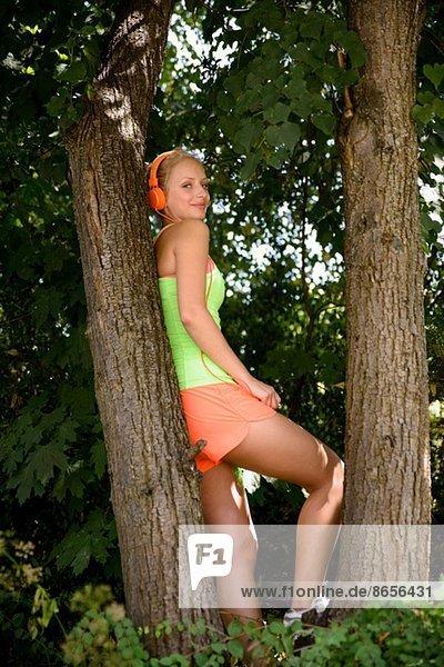 Junge Läuferin im Kopfhörer macht Pause