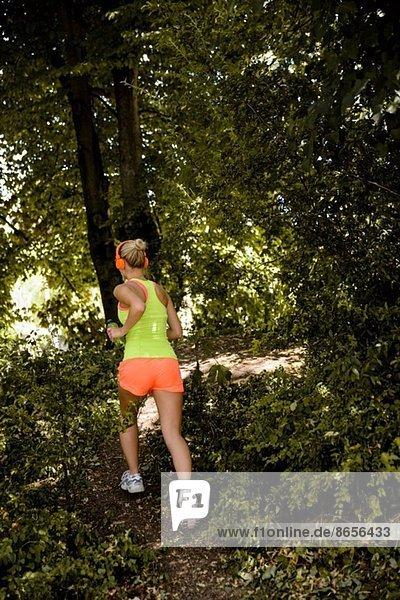 Junge Frau im Kopfhörer läuft durch den Wald