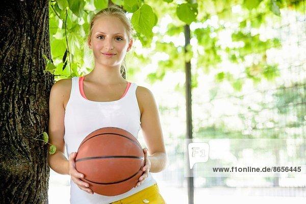 Portrait einer jungen Basketballerin im Park