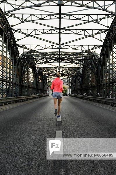 Junge Läuferin überquert Brücke