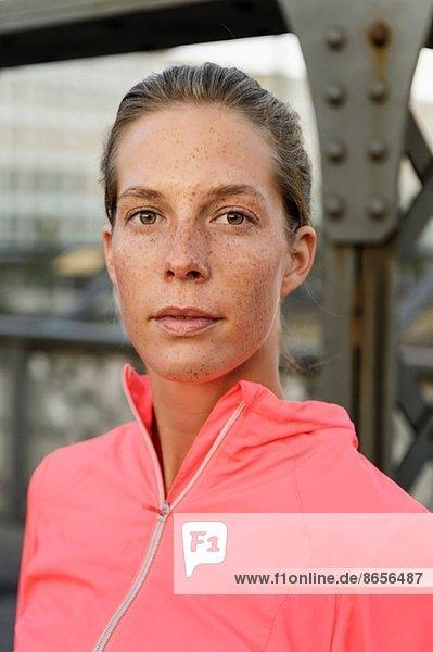 Porträt einer selbstbewussten jungen Läuferin auf der Brücke