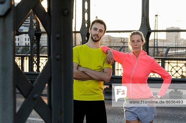 Portrait des jungen Laufpaares auf der Brücke