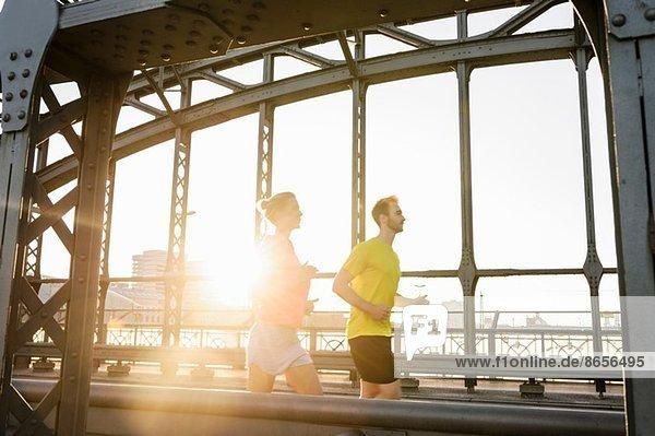 Junge Männer und Frauen laufen über die Brücke