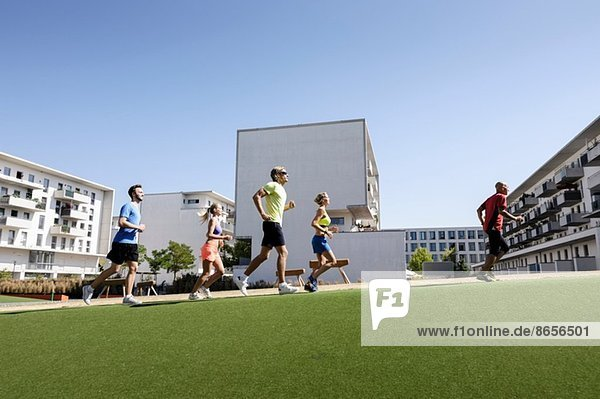 Reife Trainerin  die mit einer kleinen Gruppe von Erwachsenen im Park läuft.