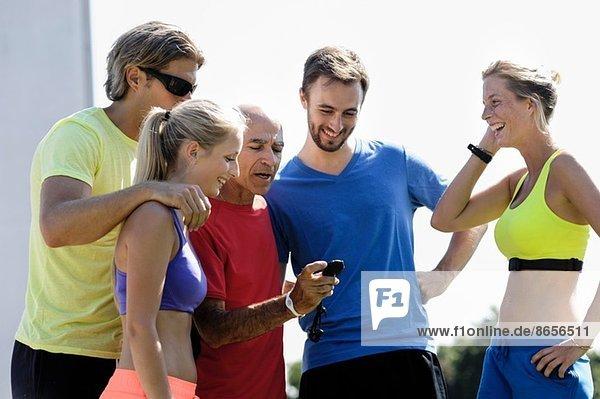 Reife männliche Trainerin und eine Gruppe erwachsener Läufer  die die Stoppuhr überprüfen.